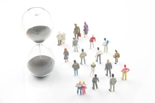 Persone in miniatura. persone diverse camminano accanto alla clessidra. durata della vita dell'umanità