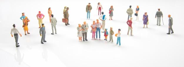 Persone in miniatura. persone diverse stanno in piedi. comunicazione della società di diverse generazioni