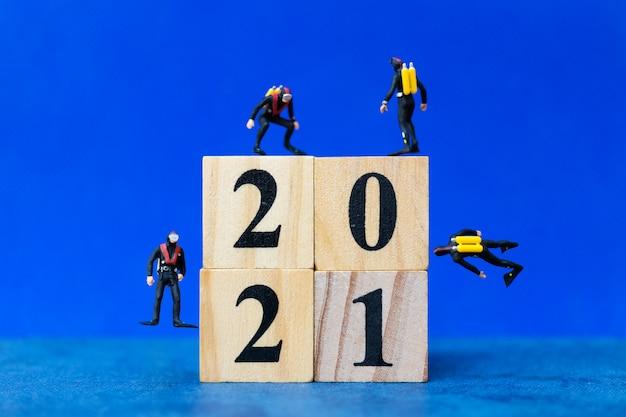 Persone in miniatura subacquei immersioni intorno al blocco di legno 2021, concetto di felice anno nuovo