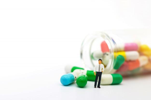 Persone in miniatura: dottore in piedi con la droga. assistenza sanitaria e concetto di business.