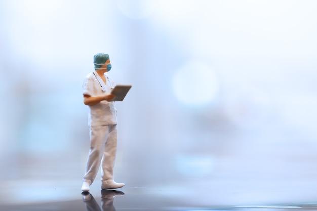 Persone in miniatura medico che indossa maschere facciali durante l'epidemia di coronavirus e influenza
