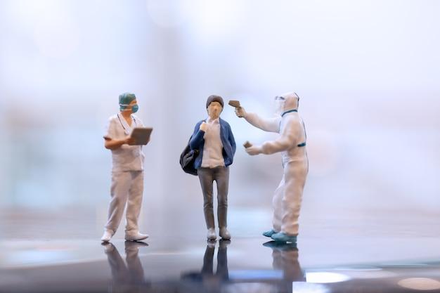 Persone in miniatura medico che indossa maschere facciali durante il coronavirus e l'epidemia di influenza.