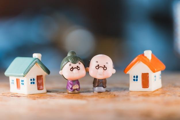 Persone in miniatura, uomo anziano e donna in piedi con mini casa utilizzando come pensionamento di lavoro e concetto di assicurazione