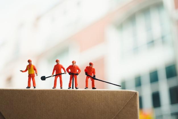 Le persone in miniatura, gli ingegneri collaborano all'azione lavorativa