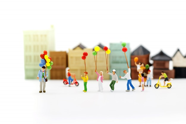 Persone in miniatura, famiglia e bambini godono con palloncini colorati, concetto felice giorno della famiglia.