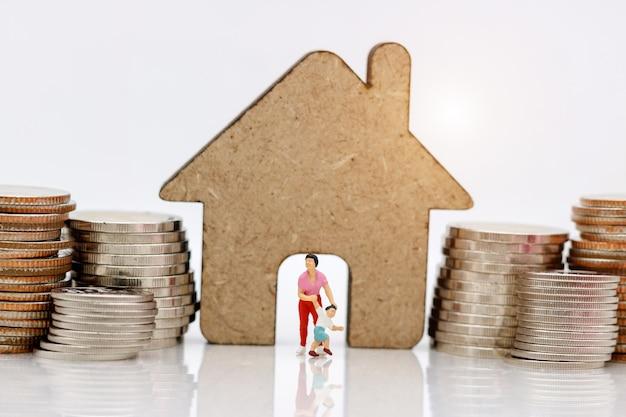 La gente in miniatura, la famiglia e i bambini si divertono con la pila di monete e casa.