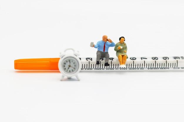 Persone in miniatura: pazienti grassi seduti su siringa e orologio. concetto di assistenza sanitaria.