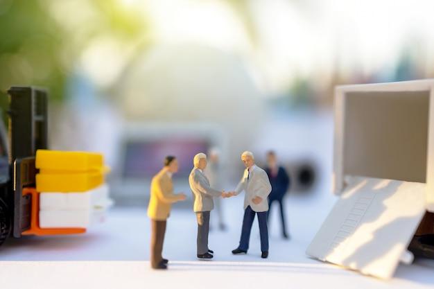 Stretta di mano di persone in miniatura per il servizio di consegna del caricatore.