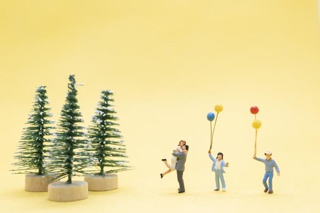 Persone in miniatura, famiglia felice che celebra un concetto di natale, natale e felice anno nuovo.