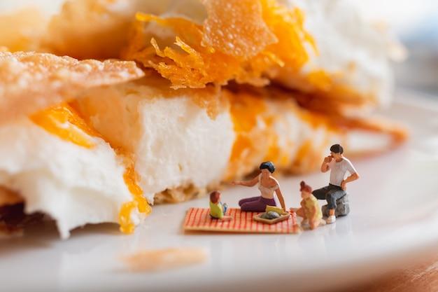 Persone in miniatura: famiglia felice seduto sul tappeto durante un picnic sul dessert
