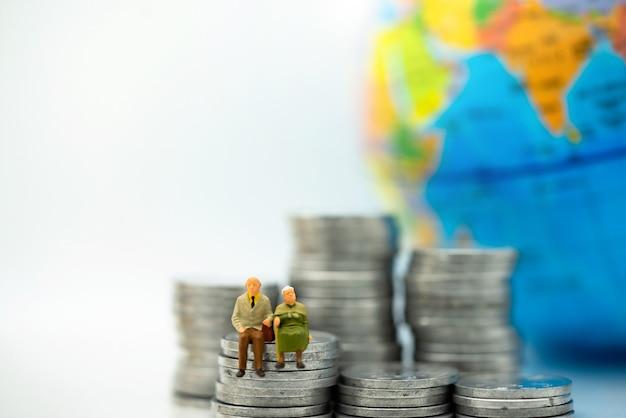 Persone in miniatura: anziani felici seduti sulla pila di monete, pensione e concetto di assicurazione sulla vita.