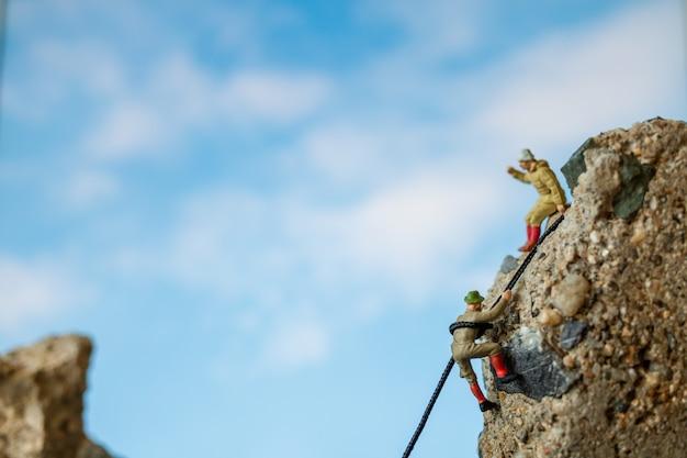 Persone in miniatura: escursionisti che si arrampicano sulla roccia. concetto di sport e tempo libero.