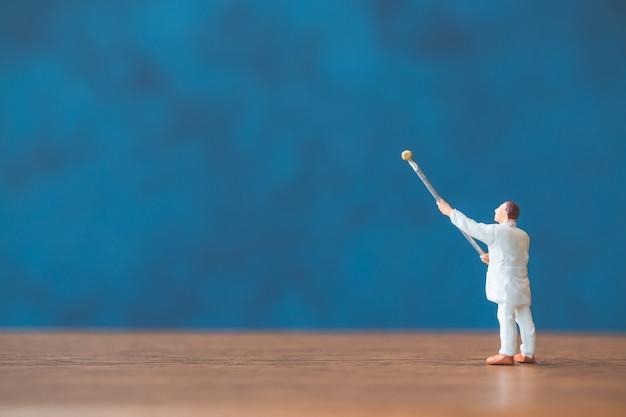 Spazzola della tenuta della gente miniatura davanti ad un fondo blu della parete