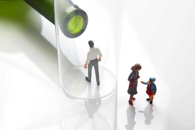 Persone in miniatura. uomo dipendente da alcol sullo sfondo di una bottiglia di vino e un bicchiere e una famiglia distrutta. il problema dell'alcolismo nella società