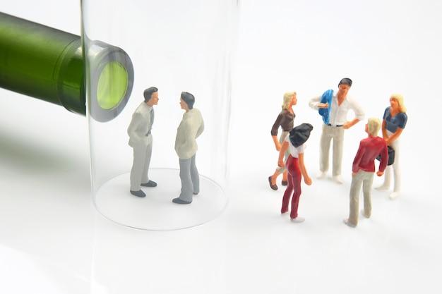 Persone in miniatura. uomo dipendente da alcol, bottiglia di vino e un bicchiere. il problema dell'alcolismo nella società e nei rapporti familiari.