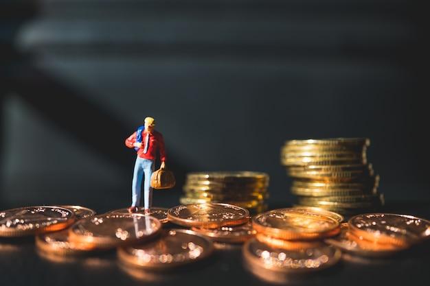 La gente miniatura, uomo che sta sulle monete della pila facendo uso come concetto di affari