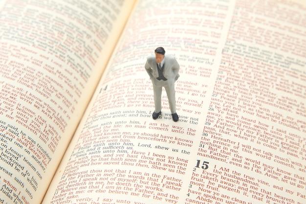 Persone in miniatura. l'uomo si trova sul testo della bibbia. cercare il sentiero della vita. io sono la via.