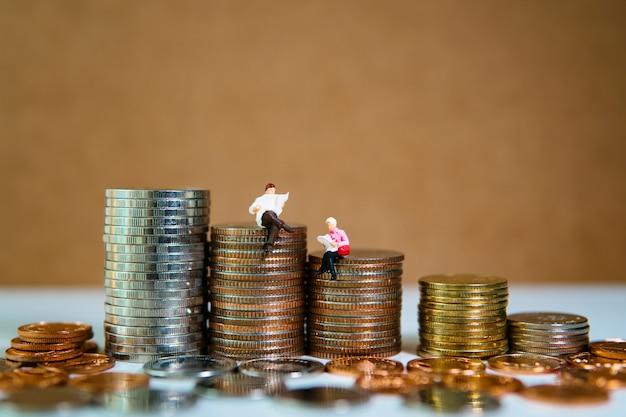 Persone in miniatura, uomo e donna che leggono sul mucchio di monete