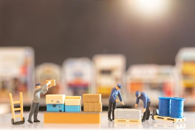 Postino in miniatura in servizio, si prepara a spedire una scatola al consumatore. servizio di consegna per il concetto di e-commerce