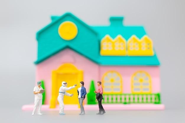 Visita medica di persone in miniatura dpi per controllare il coronavirus a casa, concetto di assistenza sanitaria