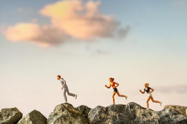 Persone in miniatura: correre su scogliera di roccia, concetti di salute e stile di vita