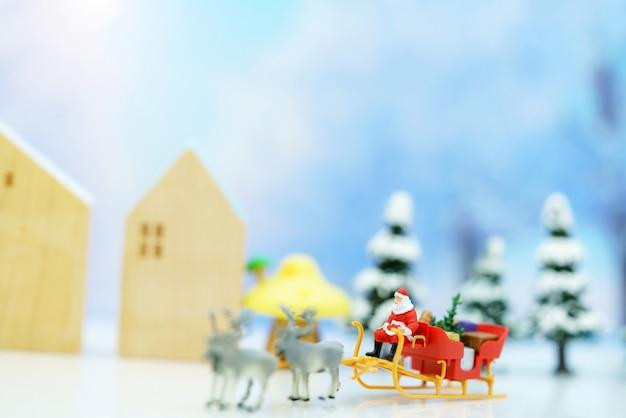 Persone in miniatura: babbo natale seduto sulla slitta di renne con auguri o cartolina postale e albero di natale.