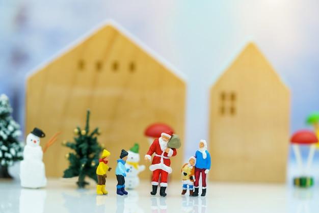 Persone in miniatura: babbo natale con i bambini che si divertono con la neve e l'albero di natale.