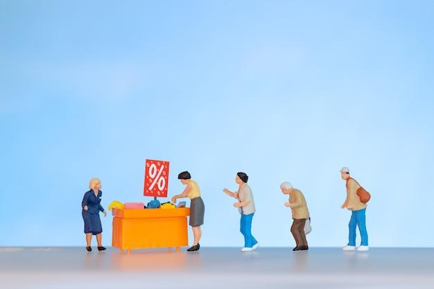 Persone in miniatura, shoppers con vassoio sconto per lo shopping di articoli scontati