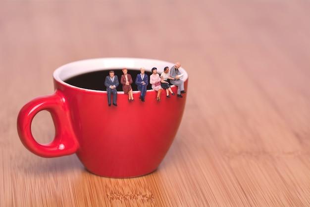 Le persone in miniatura si siedono sul bordo di una tazza di caffè, tè, caffè