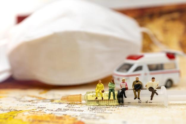Persone in miniatura siedono siringa del vaccino covid-19 con ambulanza e maschera medica e. vaccino e concetto medico sanitario.