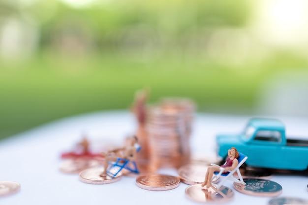 Gente miniatura che si siede sui sedili del sunbath della spiaggia e pila delle monete.