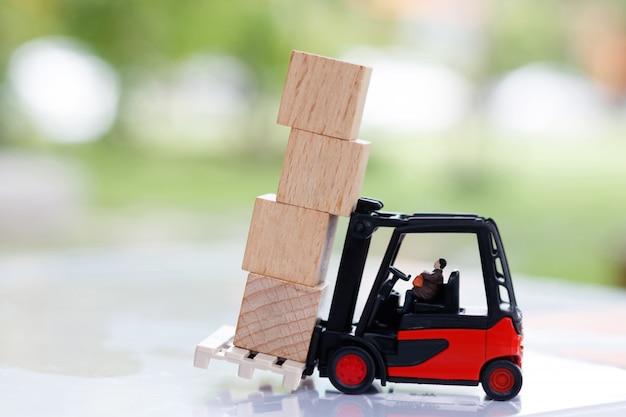 La gente in miniatura che si siede sul carrello elevatore e sposta il blocco di legno.