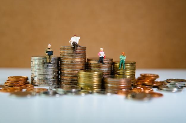 Persone in miniatura, seduto su una pila di monete