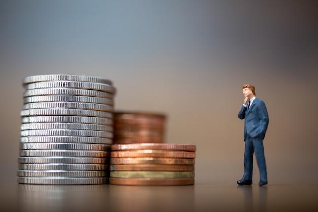 Persone in miniatura: piccoli uomini d'affari in piedi con una pila di monete, concetto di crescita aziendale.
