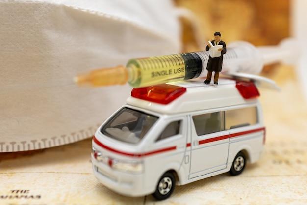 Le persone in miniatura stanno sull'auto dell'ambulanza con la maschera medica e la siringa del vaccino covid-19. vaccino e concetto medico sanitario.