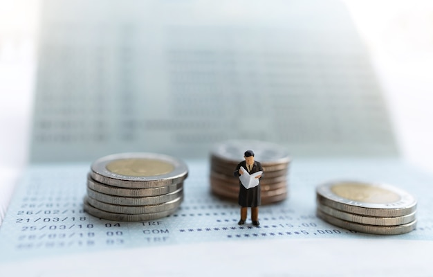 Persone in miniatura stanno sul libretto bancario e pila di monete, concetti di pensionamento.