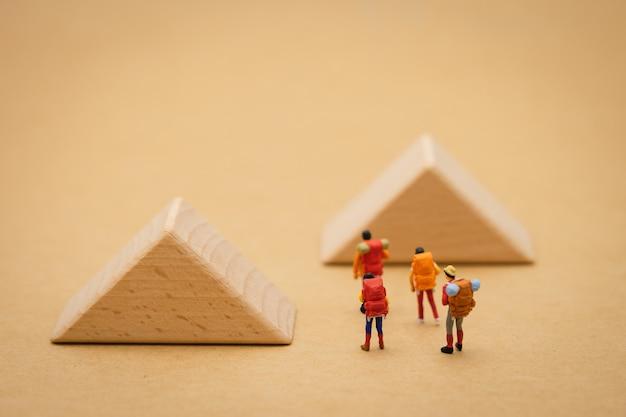 Le persone in miniatura stanno su la passerella è un blocco significa l'inizio del viaggio