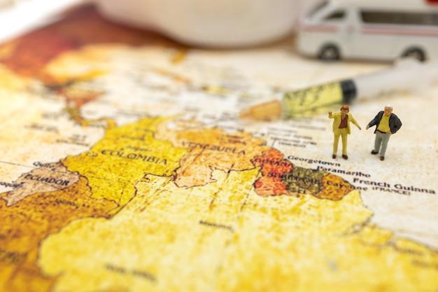 Le persone in miniatura stanno sulla mappa del mondo con l'auto ambulanza, la maschera medica e la siringa del vaccino covid-19. vaccino e concetto medico sanitario.