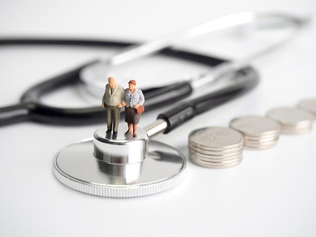 Persone in miniatura in piedi su stetoscopio medico con pila di monete.