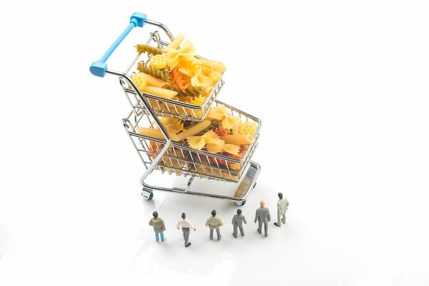 Persone in miniatura in piedi vicino a un cesto della spesa con pasta italiana su sfondo bianco