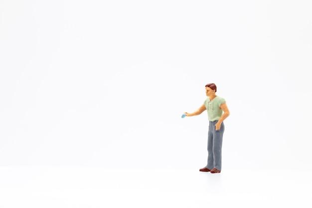 Persone in miniatura in piedi su sfondo bianco