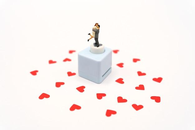Persone in miniatura in piedi con carta rossa a forma di cuore. il cuore rosso è la promessa d'amore.