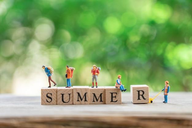Gente miniatura che sta con l'estate di legno di parola.