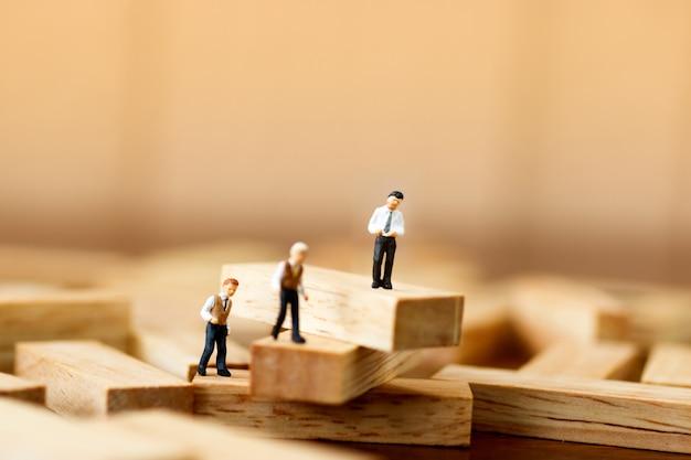 Persone in miniatura in piedi su blocchi di legno
