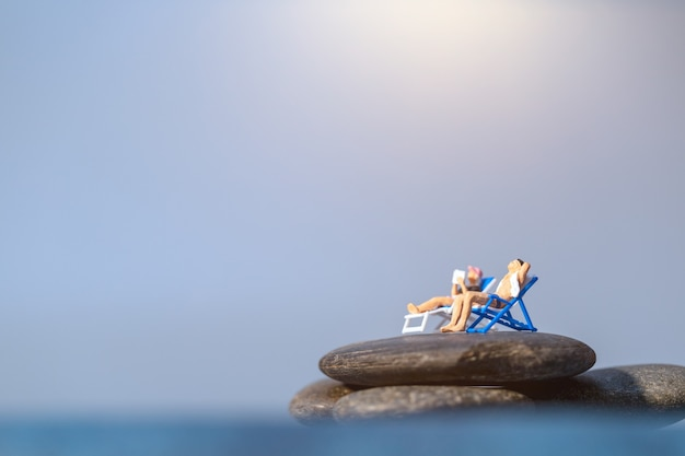 Persone in miniatura a prendere il sole sulla spiaggia, concetto di ora legale
