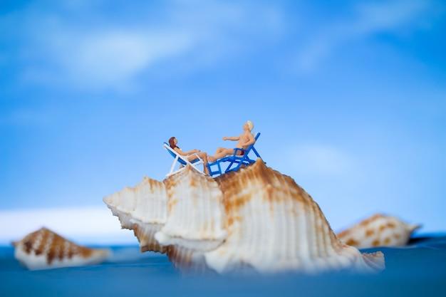 Persone in miniatura che prendono il sole su una conchiglia con sk blu