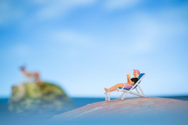 Persone in miniatura a prendere il sole su una conchiglia con cielo blu