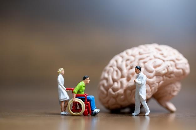 Persone in miniatura, il chirurgo ha parlato con il paziente di lesioni cerebrali. concetto di servizio medico sanitario e medico chirurgico.