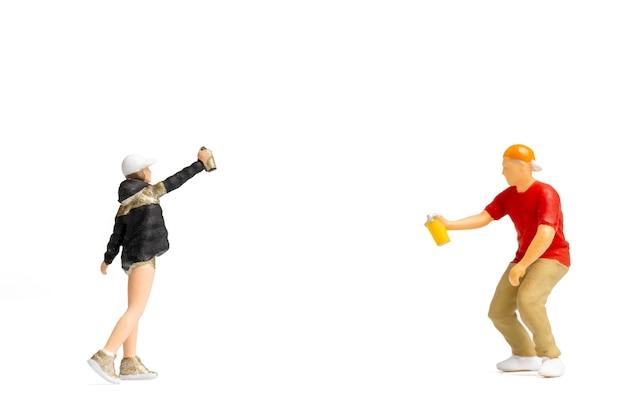 Persone in miniatura adolescente che spruzza vernice dal barattolo su sfondo bianco e spazio per il testo