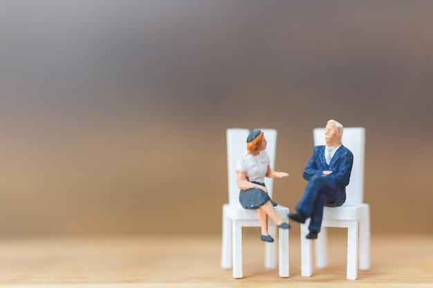 Gente miniatura che pensa alla prossima grande idea su fondo di legno